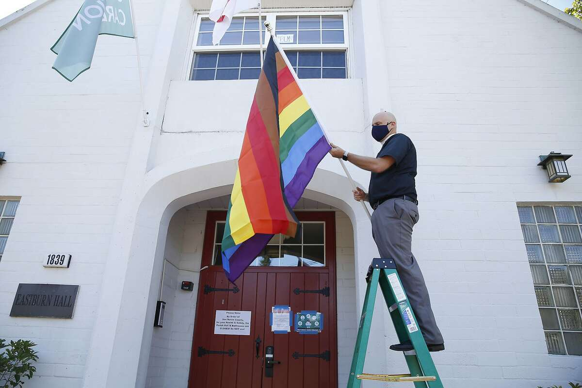 Reverend Alan Gates places a Philadelphia Pride flag at the front of the parish hall at Episcopal Church of the Epiphany on Wednesday, July 1, 2020 in San Carlos, Calif.