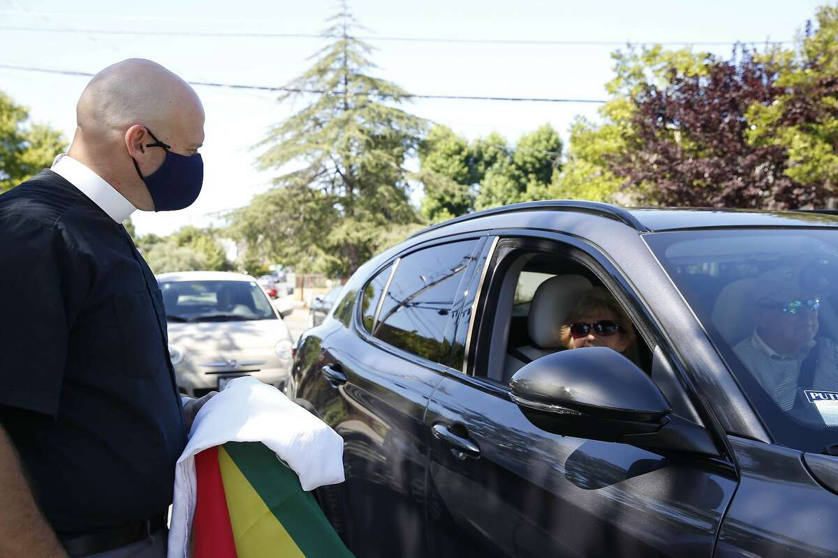 Reverend Alan Gates (l to r) talks to parishioners Betsy and Bill Koefoed of San Carlos who stopped to talk as they were driving past thet Episcopal Church of the Epiphany on Wednesday, July 1, 2020 in San Carlos, Calif.