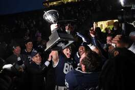 Yale's JP Shohfi, center, holds the Ivy League Championship trophy during a celebration with teammates after their 50-43 double overtime victory against Harvard in November. At left is Yale University president Peter Salovey.