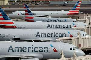 FILE - In this Wednesday, March 25, 2020, file photo, American Airlines jets sit idly at their gates as a jet arrives at Sky Harbor International Airport in Phoenix. American Airlines and four smaller carriers have reached agreement with the government for billions more in federal loans, a sign of the industrya€™s desperate fight to survive a downturn in air travel caused by the virus pandemic. The Treasury Department said Thursday, July 2, 2020, that it had finalized terms of new loans to American, Spirit Airlines, Frontier Airlines, Hawaiian Airlines and SkyWest Airlines. (AP Photo/Matt York, File)