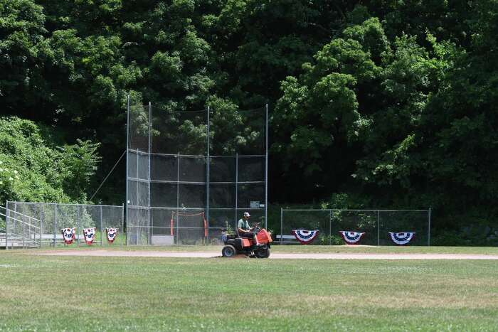 A Greenwich town employee mows the grass at the baseball field at Pemberwick Park in the Pemberwick section of Greenwich, Conn. Thursday, July 2, 2020. Starting Monday, residents will be allowed to use the town's baseball diamonds, soccer fields, and basketball courts.