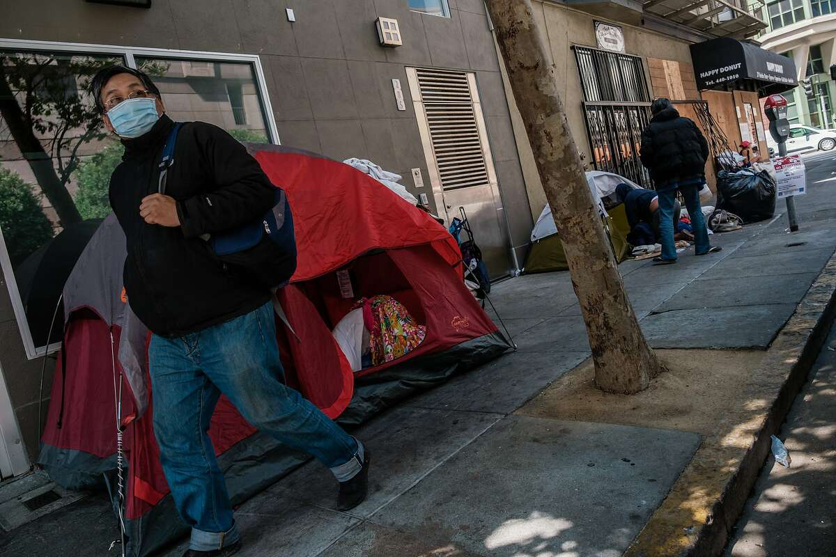 A pedestrian walks past a small tent encampment on the corner of Taylor and Ellis in San Francisco on Tuesday, July 2, 2020.
