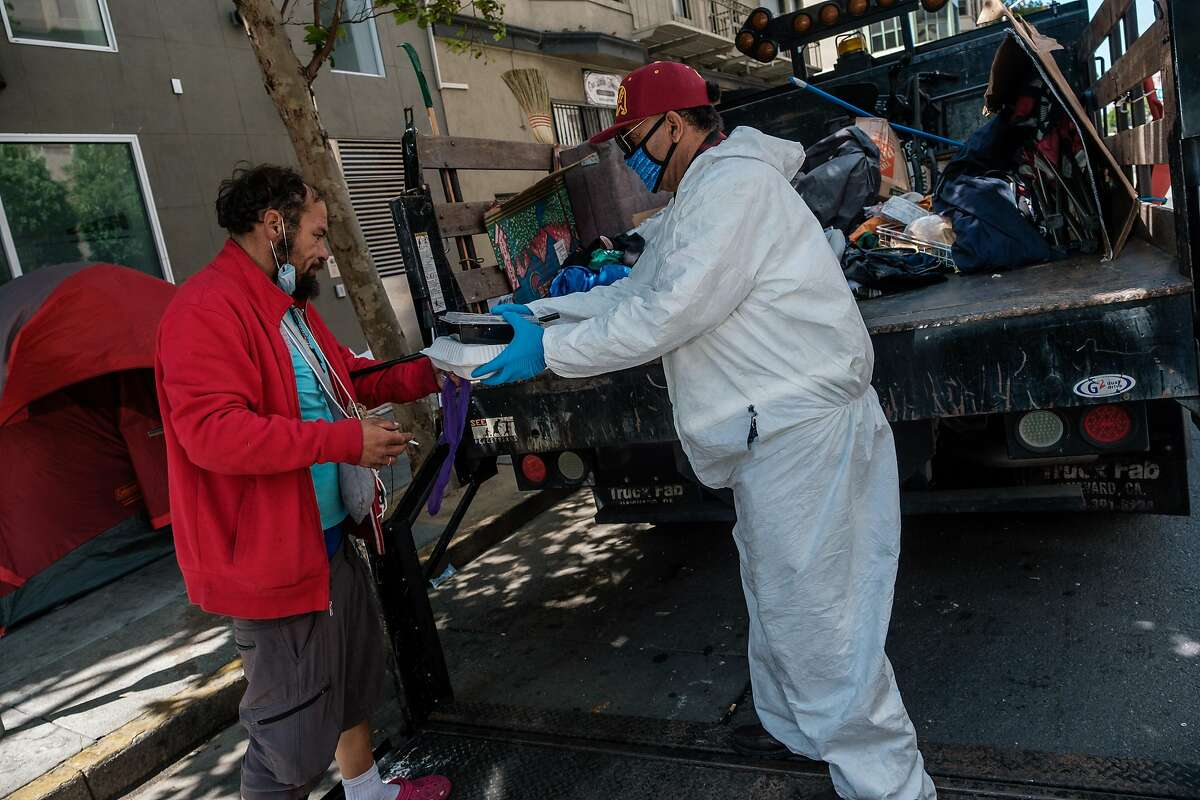 City employee Abdul, helps Eric Delahonssaye who is staying in a small tent encampment on the corner of Taylor and Ellis clean up his trash in San Francisco on Tuesday, July 2, 2020. Mr. Delahonssaye is waiting to be moved into a hotel being made available to homeless.