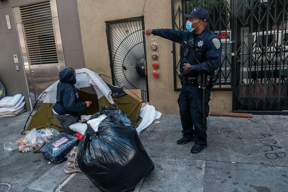 Officer B. Holbrook speaks to a woman staying in a small tent encampment on the corner of Taylor and Ellis about moving to a hotel in San Francisco on Tuesday, July 2, 2020.