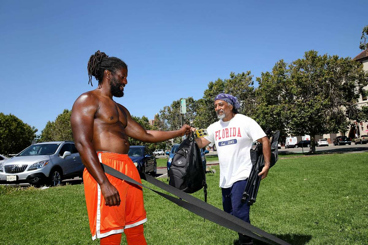 Fitness instructor Brendan Bailey, left, converses with Morgan Tyson, 68, of Oakland, after Tyson wraps up a work out at Lakeshore Park in Oakland, Calif., on Tuesday, June 30, 2020. When gyms closed across the Bay Area, fitness instructor Brendan Bailey started going to Lakeshore Park at Lake Merritt every morning at 10 a.m. to do pull ups. Over time, a few other people started joining him. As the group grew, a community formed: strangers crowdsourced equipment and sanitation supplies, ran workout stations, and cheered on each other. They now bring their kids to play in the park. With many Bay Area gyms limiting operations to gear up to a safe reopening, and many other closing permanently (including 13 Bay Area 24 hour Fitness locations), this community is asking: