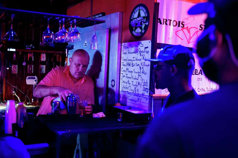 In this June 8, 2020, file photo, Rodney Ott, owner of The Loft, makes mixed drinks from behind the bar for patrons as he reopens fully for the first time amid the coronavirus outbreak in downtown Flint, Mich. Authorities are closing honky tonks, bars and other drinking establishments in some parts of the U.S. to stem the surge of COVID-19 infections -- a move backed by sound science about risk factors that go beyond wearing or not wearing masks. (Jake May/The Flint Journal via AP, File) / The Flint Journal, MLive.com