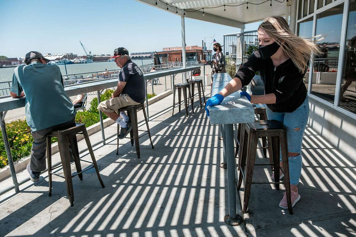 Megan Keeton sterilizes the patio furniture at Mare Island Brewing Taproom in Vallejo on Thursday, July 2, 2020.