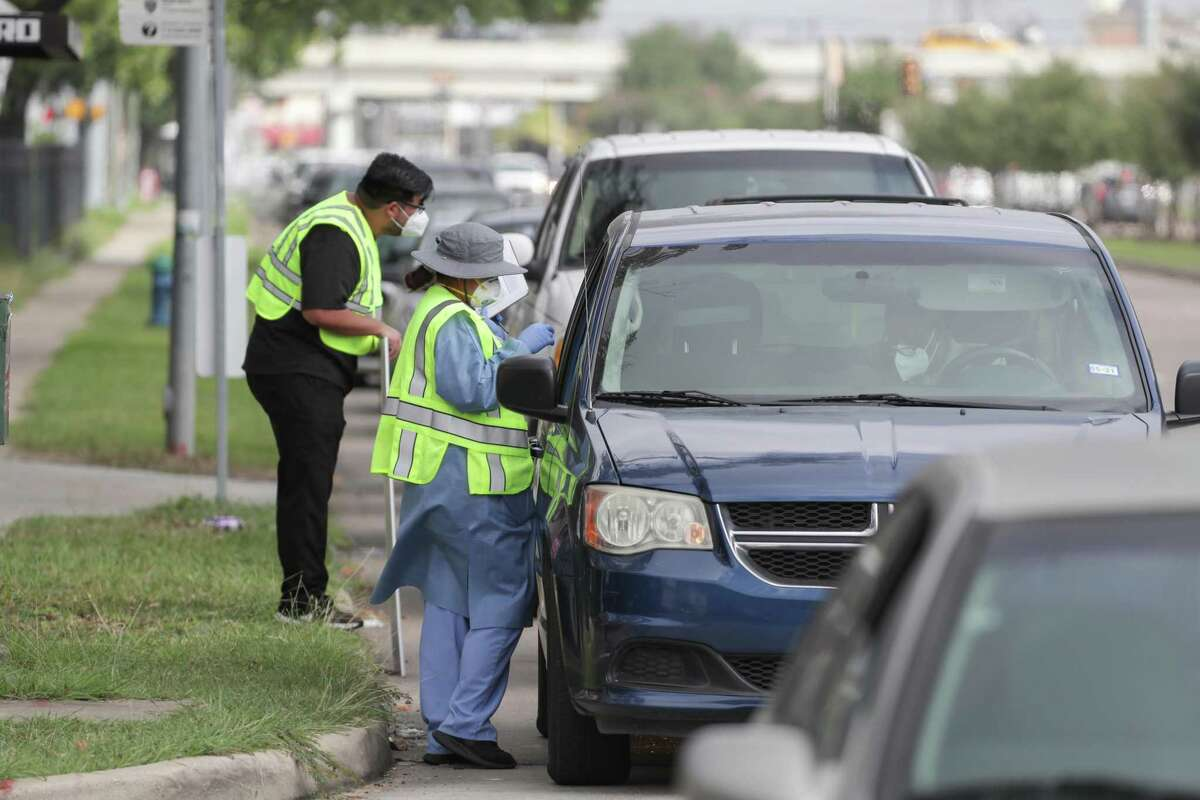 My Family Doctor medical assistants Nestor Quilantan and Perla Hilgera offered encouragement and checked in people who wanted to be tested for COVID-19 Thursday, July 2, 2020, in Houston. The long line of cars with people wanting to be tested stretch from the site to and on to the 59 off ramp.
