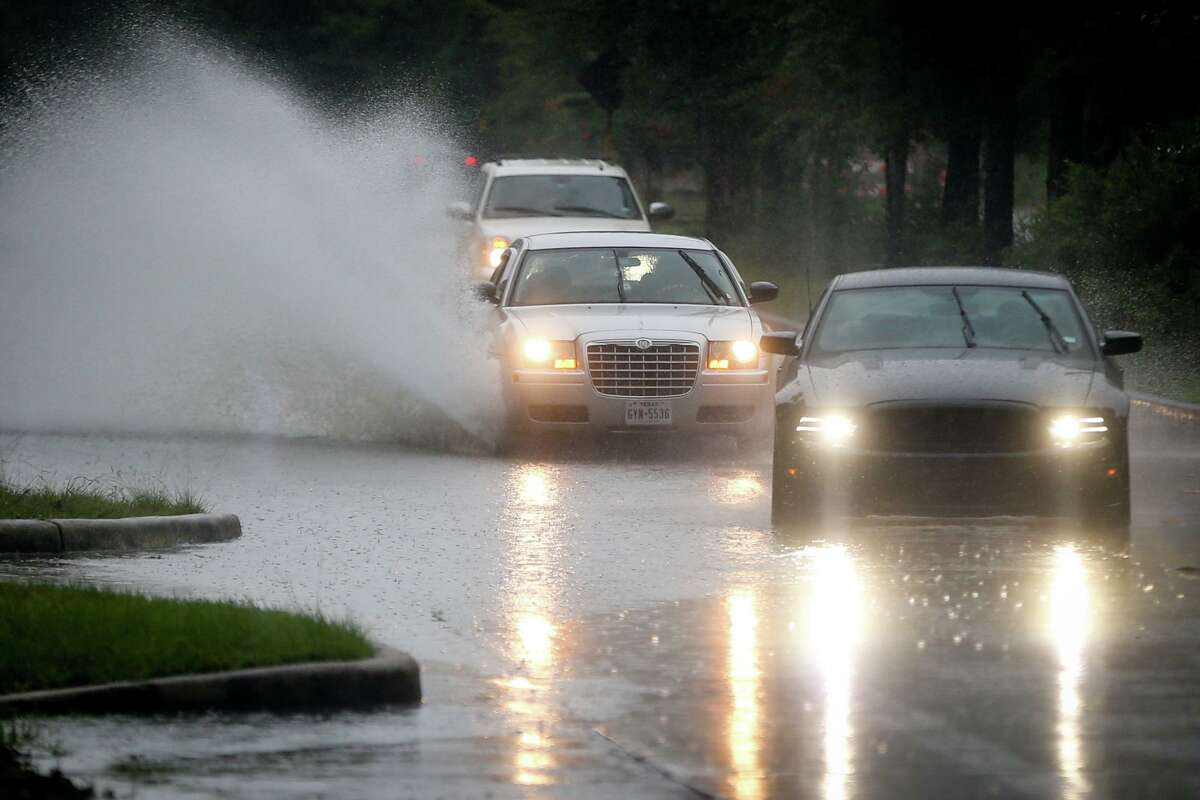 Cars navigate around and through high waters on Research Forest Drive near Crownridge Drive after heavy rain Monday, July 10, 2017, in The Woodlands.