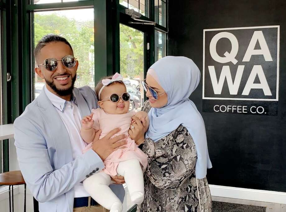 Qawa Coffee Co. co-owners Abdul Alhadheri, left, and his wife, Amirah Ailaqi,hold their daughter at the 170 Main St., Middletown, cafe. Photo: Qawa Coffee Co.