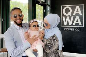 Qawa Coffee Co. co-owners Abdul Alhadheri, left, and his wife, Amirah Ailaqi,hold their daughter at the 170 Main St., Middletown, cafe.