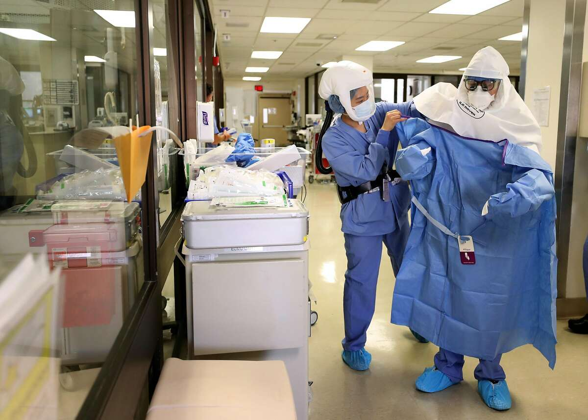 SAN JOSE, CALIFORNIA - MAY 21: (EDITORIAL USE ONLY) A nurse helps a doctor put on his personal protective equipment (PPE) before performing a procedure on a coronavirus COVID-19 patient in the intensive care unit (I.C.U.) at Regional Medical Center on May