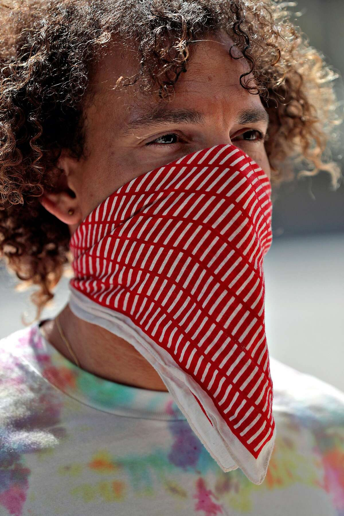Solomon Eversole wearing a mask made of a folded handkerchief with a piece of polyester cloth between the two folds in Monclair Village in Oakland, Calif., on Tuesday, June 30, 2020. As more positive test results show a spike in the coronavirus infections, people wanting to get outside are wearing masks to prevent the spread of the disease.