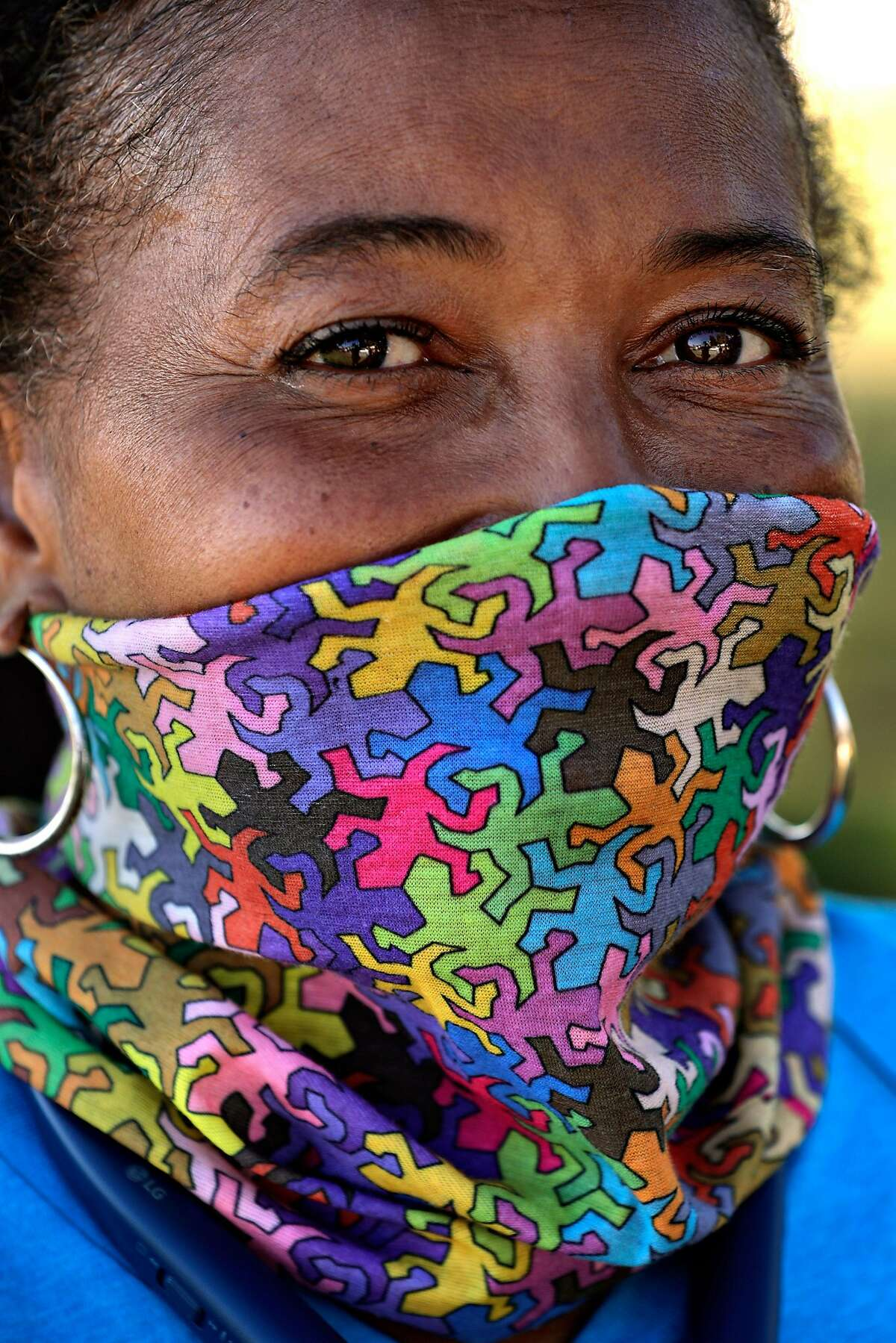 Stacey, no last name given, wearing a cloth mask at Lake Merritt in Oakland, Calif., on Tuesday, June 30, 2020. As more positive test results show a spike in the coronavirus infections, people wanting to get outside are wearing masks to prevent the spread of the disease.
