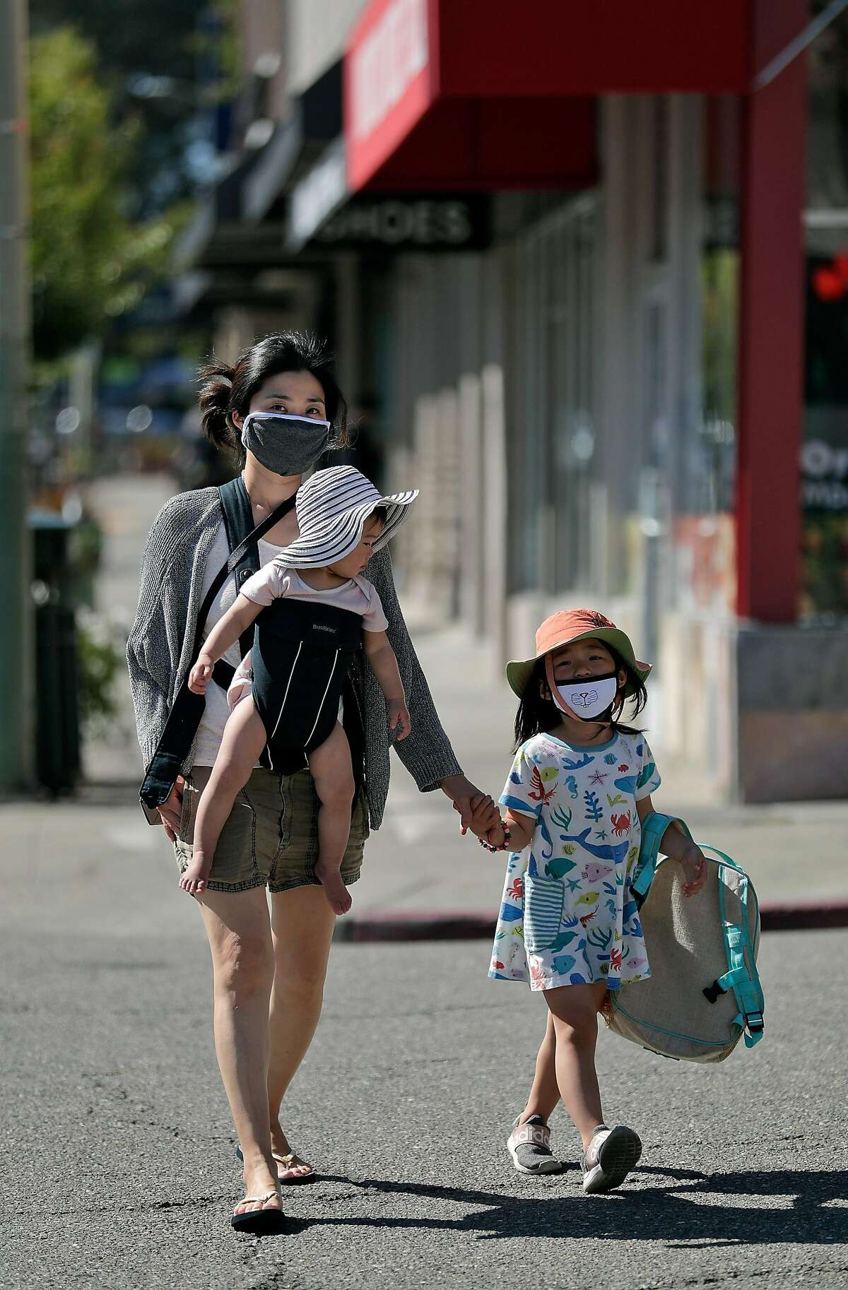 Dawn Sung walks with her daughters Elena, in carrier, and Astrid Chen wearing a mask in Monclair Village in Oakland, Calif., on Tuesday, June 30, 2020. As more positive test results show a spike in the coronavirus infections, people wanting to get outside are wearing masks to prevent the spread of the disease.