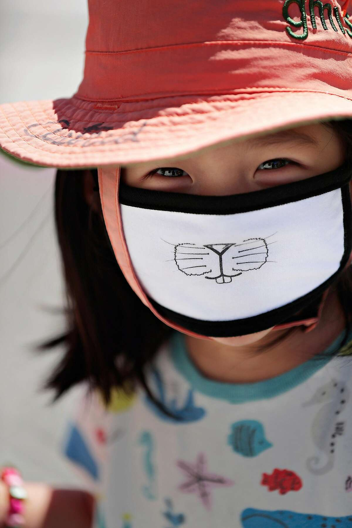 Astrid Chen smiles as she wears a mask with her mom in Monclair Village in Oakland, Calif., on Tuesday, June 30, 2020. As more positive test results show a spike in the coronavirus infections, people wanting to get outside are wearing masks to prevent the spread of the disease.