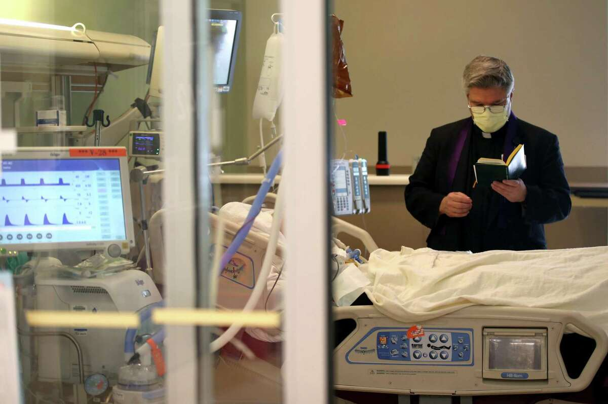 Father Barry O'Toole reads a prayer to a patient in the intensive care unit on May 21 at Regional Medical Center in San Jose.