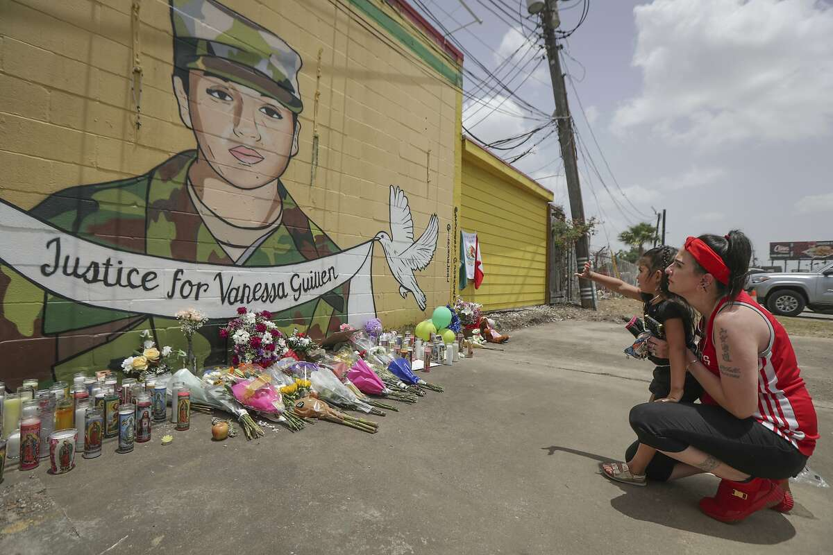 """Dawn Gomez holds her 3-year-old granddaughter, Saryia Greer, who waves at Vanessa Guillen's mural painted by Alejandro """"Donkeeboy"""" Roman Jr. on the side of Taqueria Del Sol, Thursday, July 2, 2020, in Houston. Army investigators believe Guillen, a Texas soldier missing since April, was killed by another soldier on the Texas base where they served, the attorney for the missing soldier's family said Thursday. (Steve Gonzales/Houston Chronicle via AP)"""