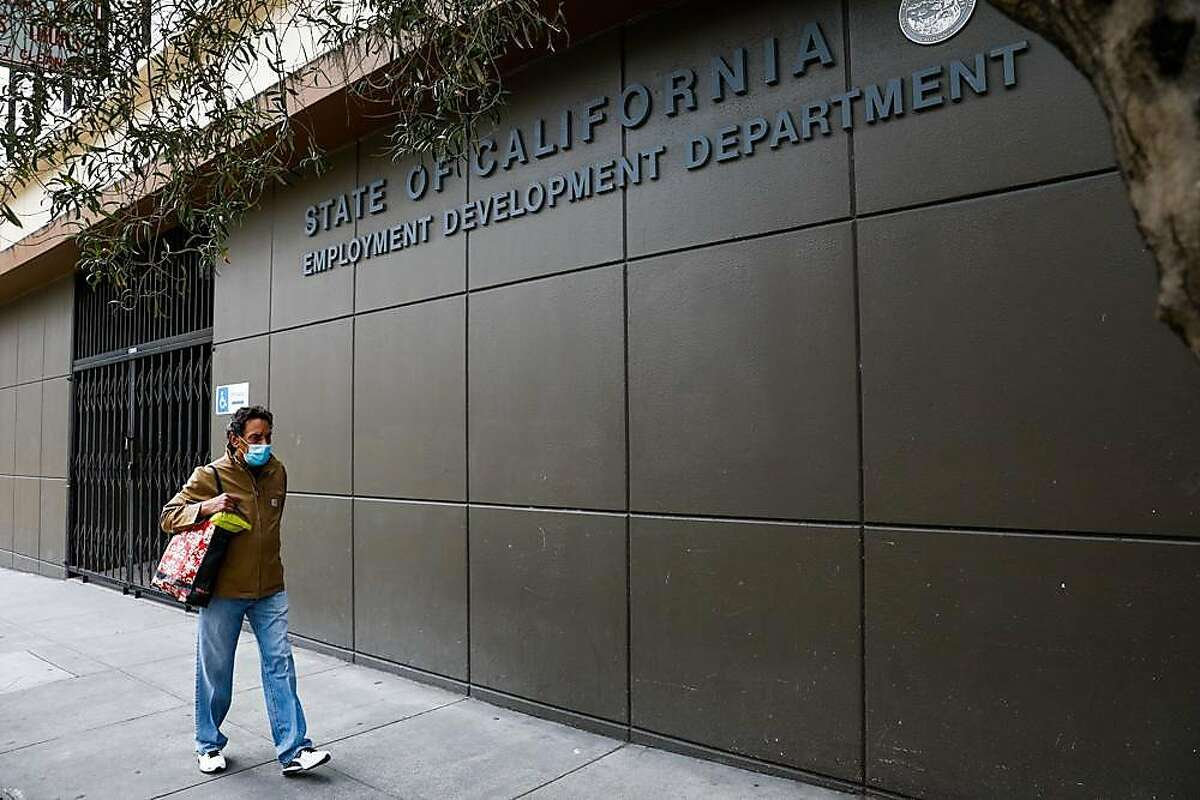 A man walks by the Employment Development Department office in San Francisco in June. People trying to file new claims or certify jobless claims so that benefits would continue were frustrated this weekend when the EDD website went down.