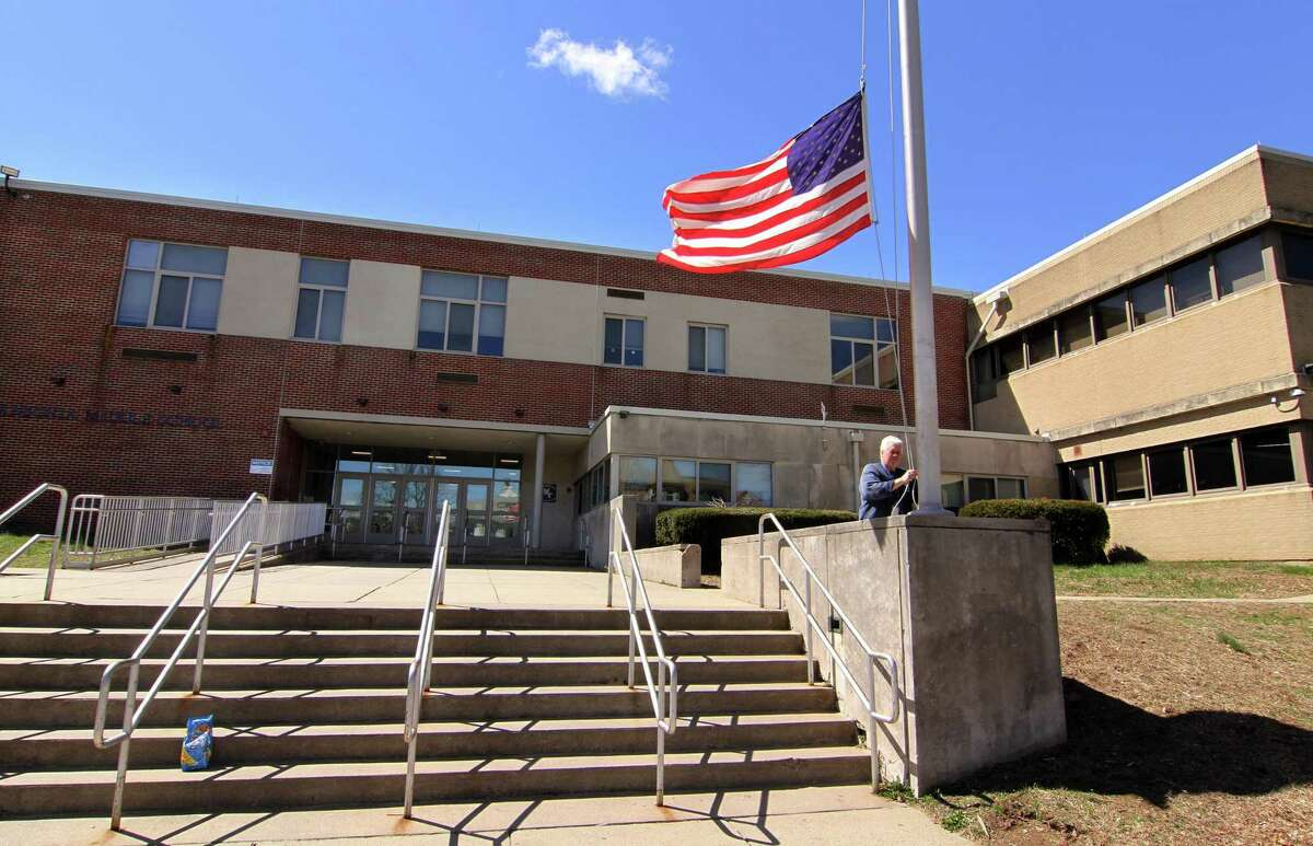 In this file photo, Brian Turner retires the flag in front of Ansonia Middle School on Howard Ave in Ansonia, Conn., on Thursday April 11, 2019.