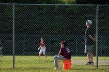 A player sits on a bucket set out for players to use in place of the dugouts which are closed as part of the precautions in place for softball and baseball. Thursday, July 2, 2020, in New Milford, Conn.
