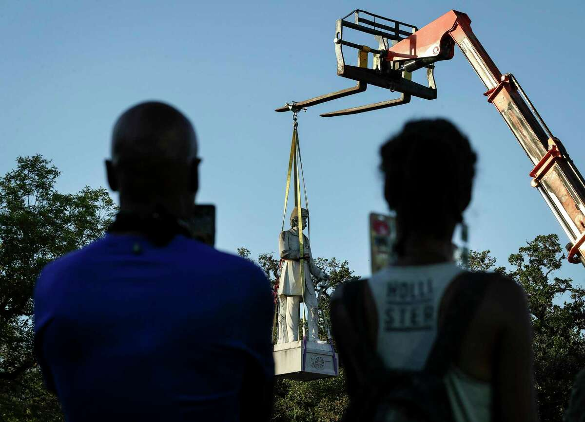 """Qenuziri Zmahtanen, left, and his wife Maakamma, watch as a statue of Richard """"Dick"""" Dowling is removed Wednesday, June 17, 2020, at Hermann Park in Houston. Dowling was a Confederate officer who defeated a Union force at Sabine Pass in 1863 during the Civil War. """"It's the significance of the world recognizing the offensiveness of these Confederate statues,"""" Maakamma Zmahtanen said. """"We don't see any of our ancestors up, who built this country,"""" she said. The statue was Houston's first public art work, dedicated March 17, 1905 on Market Square, and was later moved to Hermann Park in 1958, according to a plaque that was also removed."""