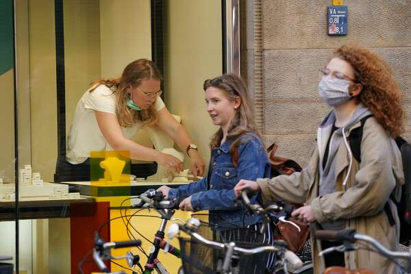 LEIPZIG, GERMANY - APRIL 20: Two young women. one of whom is wearing a protective face mask, walk past a shop assistant preparing a window display in a watches and jewellery store open for the first time since March on the first day of the easing of some restrictions during the coronavirus crisis on April 20, 2020 in Leipzig, Germany. Across Germany today many states, but not all, are introducing steps to lift restrictions that have had a deep economic and social impact, including the reopening of smaller-size stores, allowing high school students to take exams and restarting production lines in some factories. The number of Covid-19 infections is continuing to rise, but at a slower rate than in previous weeks, which is giving the federal and state governments hope that the time is right to begin lifting restrictions. (Photo by Sean Gallup/Getty Images)