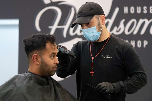 A barber wearing a face mask cuts a customer's hair in Wellington on May 14, 2020. - New Zealand will phase out its coronavirus lockdown over the next 10 days after successfully containing the virus, although some restrictions will remain, Prime Minister Jacinda Ardern announced on May 11. Ardern said that from May 14 shopping malls, restaurants, cinemas and playgrounds will reopen -- with the country moving to Level Two on its four-tier system. (Photo by Marty MELVILLE / AFP) (Photo by MARTY MELVILLE/AFP via Getty Images)