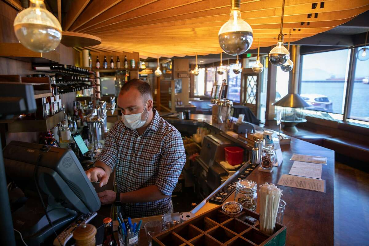Drew Bernier checks on an online order at Scoma's Restaurant on Tuesday, June 30, 2020, in San Francisco, Calif. Businesses along the Fisherman�s Wharf and Pier 39 are reportedly operating at around 20% the usual amount and struggling without the usual massive daily flood of tourists, amid the coronavirus pandemic. Bernier is the assistant general manager and beverage director at Scoma�s Restaurant.