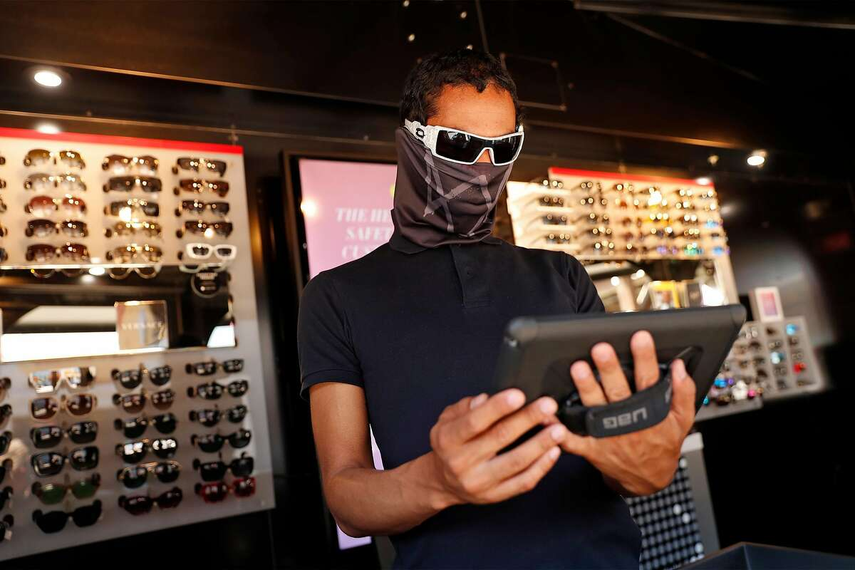 Mitchell C. Robinson II looks at a tablet while waiting for customers at Sunglass Hut on Pier 39 in San Francisco, Calif., on Wednesday, July 2, 2020. The Bay Area and California are struggling to control the coronavirus after having success with shelter in place earlier in 2020.