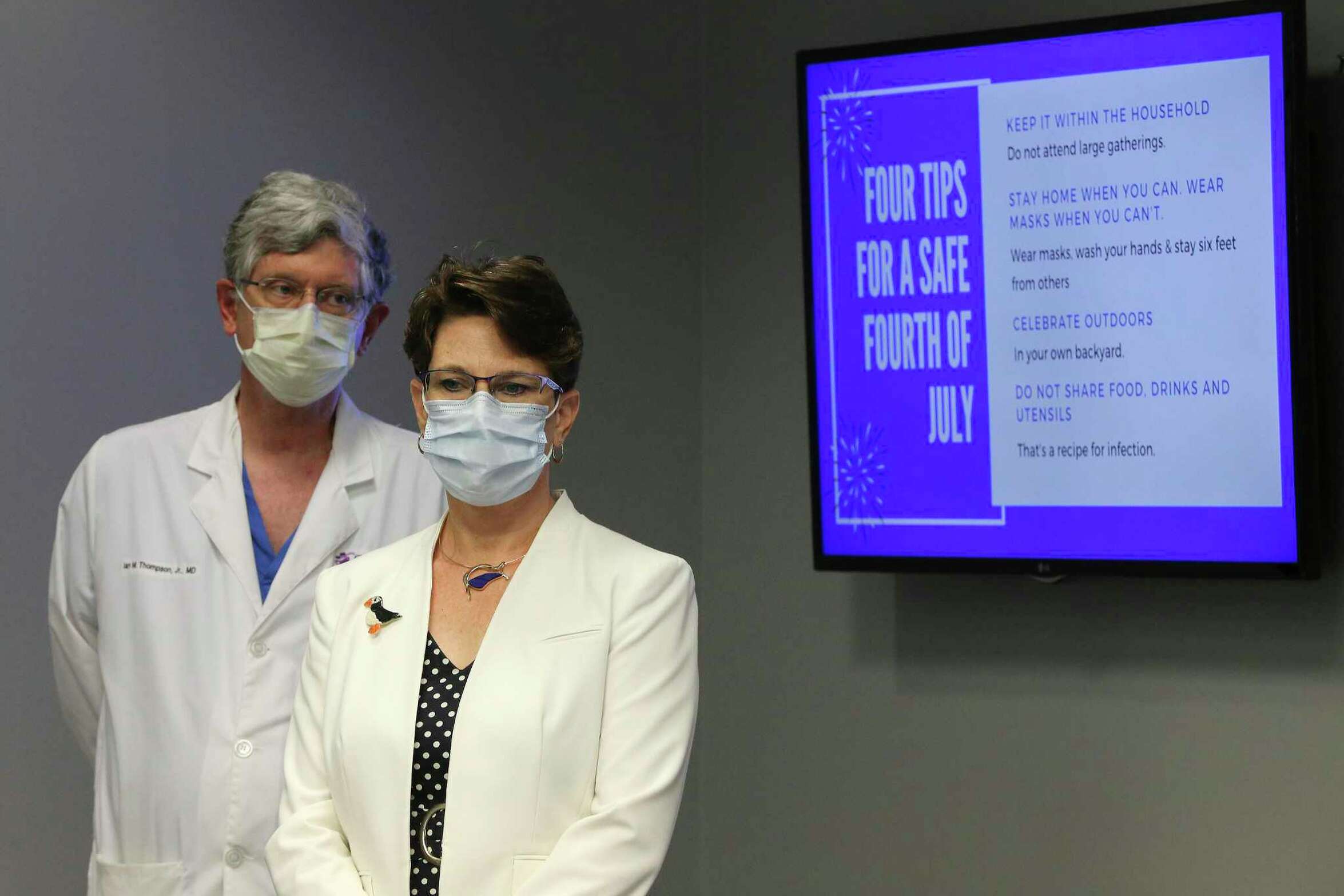 Dr. Colleen Bridger and Dr. Ian Thompson, III, CEO of Christus Medical Center stand near a screen providing safety tips for celebrating the 4th of July weekend.