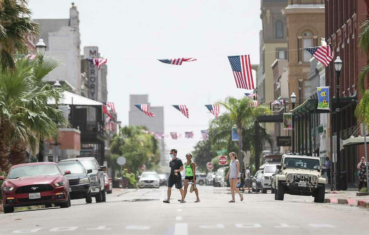 People walk across Postoffice Street on Wednesday, July 1, 2020, in Galveston.