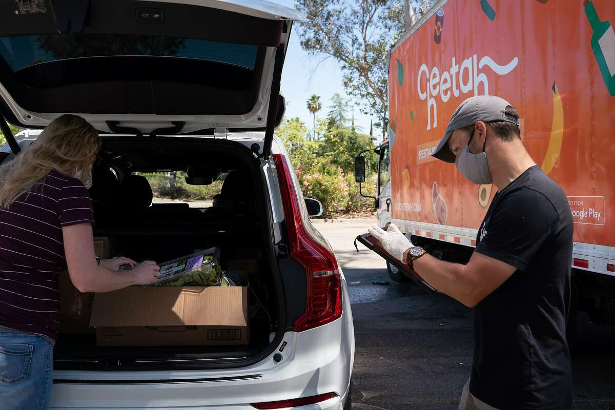 Chelsey Lost, 37, of Livermore, left, picks up a grocery order from Byron Eppler, 35, a customer success specialist with Cheetah food supply, in Pleasanton, Calif., on Tuesday, June 16, 2020.