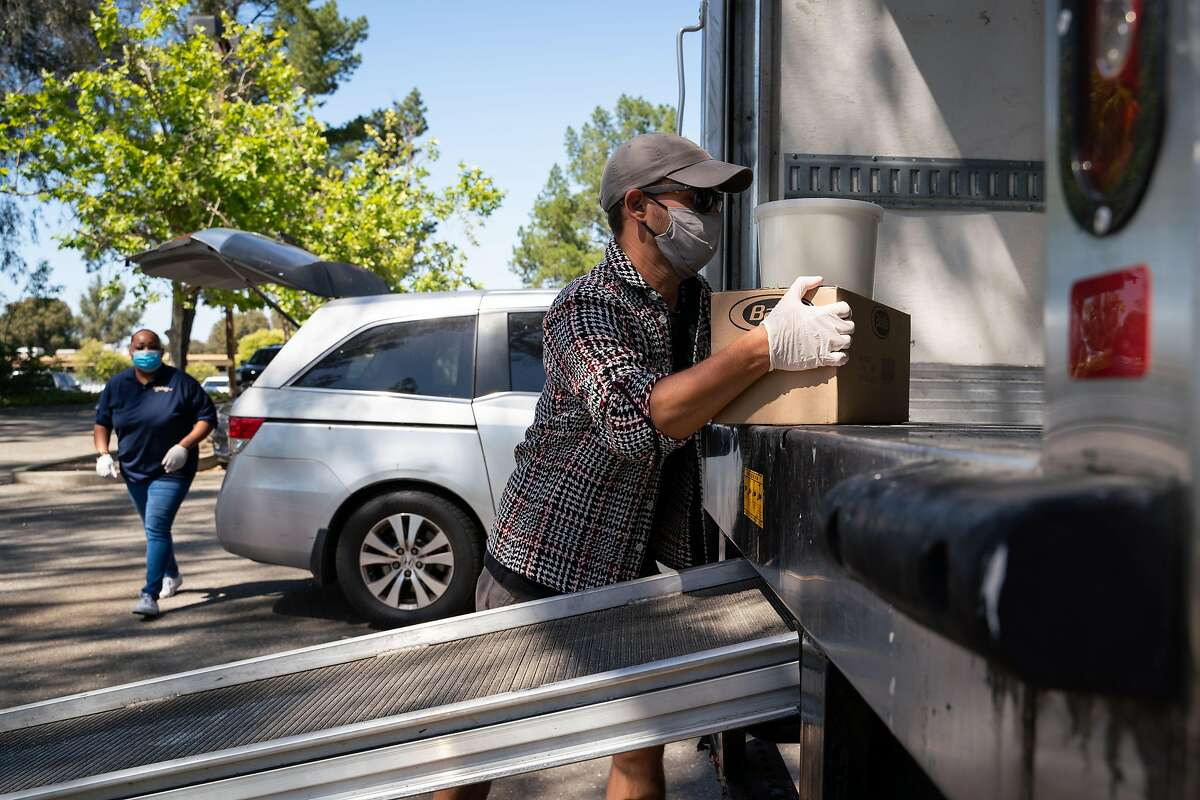 Cheetah employees Nina Oppenheimer, 38, left, and Byron Eppler, 35, prepare a customer order at a pick-up location in Pleasanton, Calif., on Tuesday, June 16, 2020.