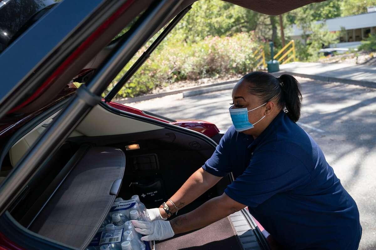 Cheetah employee Nina Oppenheimer, 38, of Stockton, loads bottled water into a customer's car in Pleasanton, Calif., on Tuesday, June 16, 2020.