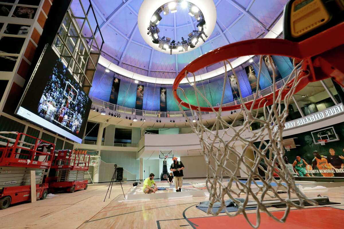 Workers perform restorations at the Naismith Memorial Basketball Hall of Fame, in Springfield, Mass., Tuesday, June 23, 2020. The museum is scheduled to reopen in the beginning of July 2020 with a whole new look after a $22 million renovation. (AP Photo/Steven Senne)