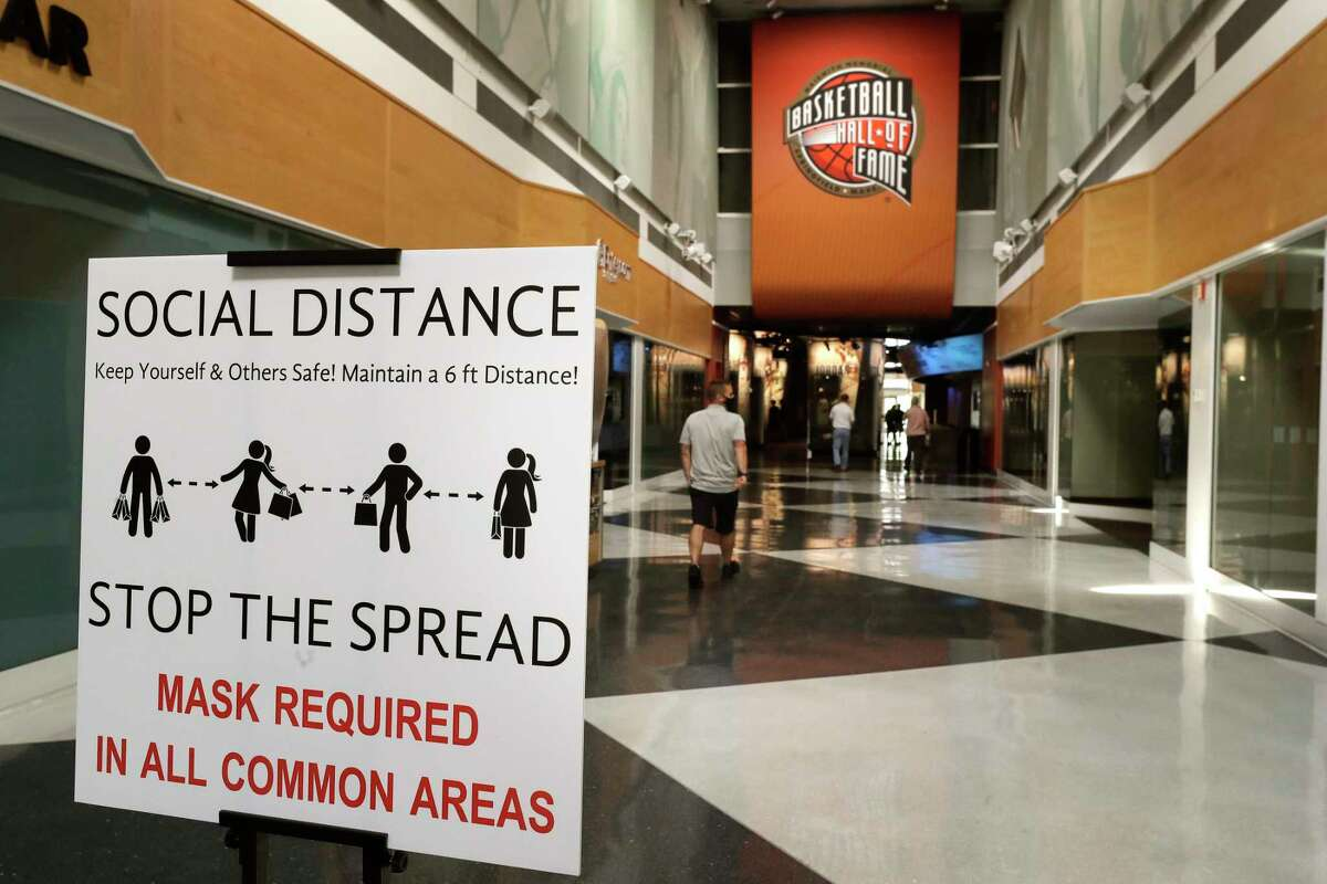 A sign advising safety measures for the coronavirus stands near an entrance to the Naismith Memorial Basketball Hall of Fame, in Springfield, Mass., Tuesday, June 23, 2020. The museum is scheduled to reopen in the beginning of July 2020 with a whole new look after a $22 million renovation. (AP Photo/Steven Senne)