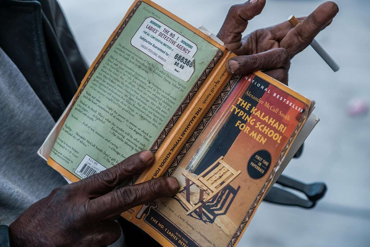 """A close up of the book that John """"Eric"""" Pradd reads as he sits near the corner of Turk and Van Ness in San Francisco on Friday, June 26, 2020. Mr. Pradd has had the same routine for years, he will sit between Books Inc. and Peete's Coffee, up against the same tree and read all day long making sure to greet each passerby with a friendly, """"Good afternoon."""""""