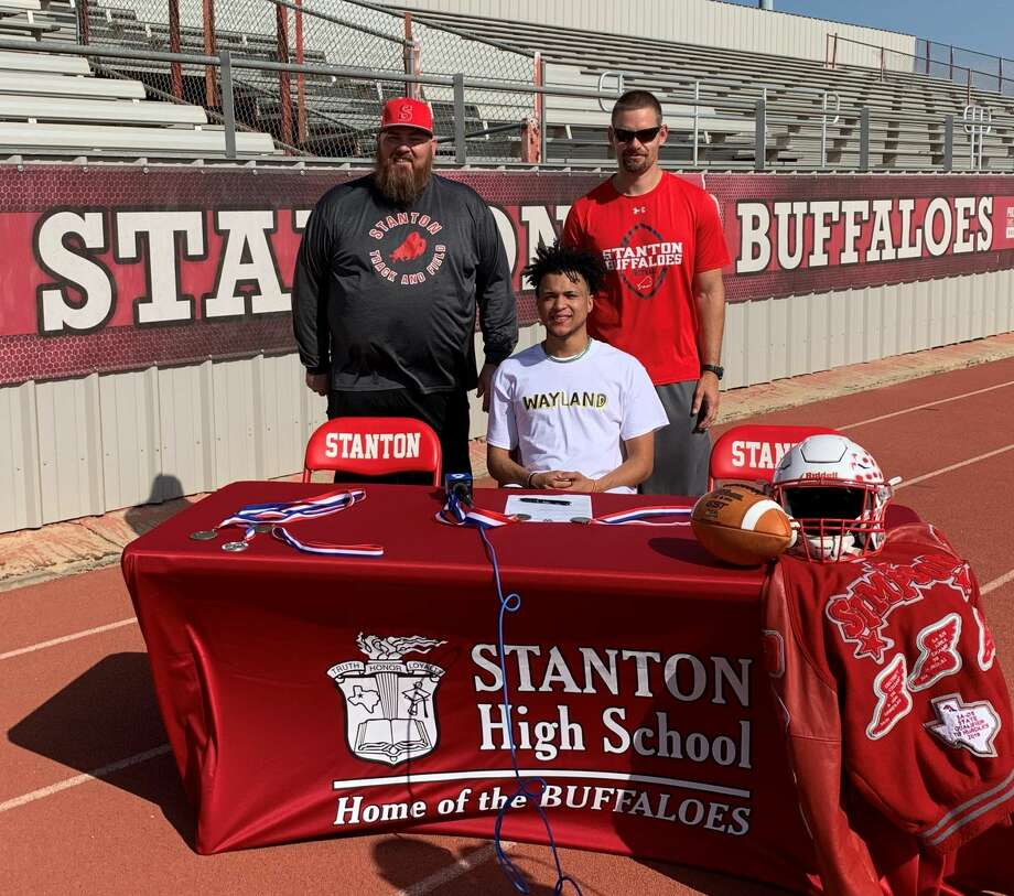 Stanton High School athlete Devan Simpson (seated) signs commits to Wayland Baptist University to play football and run track. Stanton track coach Graden Long, left, and Stanton football coach Cody Hogan, right, join him at Buffalo Stadium on Thursday. Photo: Courtesy Photo