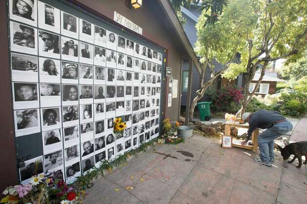 A neighbor takes a Black Lives Matter sign from a memorial altar Neeka Salmasi created on the garage door of a Berkeley Hills home in Berkeley, Calif. on July 2, 2020. The Black Lives Matters altar honoring the lives of African-Americans killed by police officers across the United States. Photo: Douglas Zimmerman/SFGATE / SFGATE