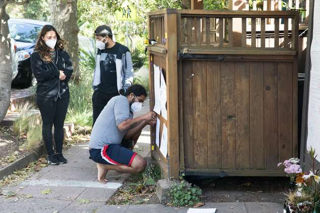 Michael Anand Manoharan-Valerrio puts up informational signs as friends Valerie Alphin and Eduardo Peralta look on. They helped Neeka Salmasi create a Black Lives Matters altar honoring the lives of African-Americans killed by police officers on the garage door of a Berkeley Hills home in Berkeley, Calif. on July 2, 2020. Photo: Douglas Zimmerman/SFGATE / SFGATE