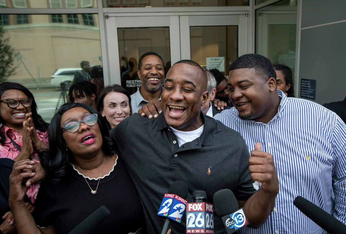 Lydell Grant, center, his mother Donna Poe, center-left, and brother Alonzo Poe, center-right, talk to reporters after Grant's release on bond on Tuesday, Nov. 26, 2019, in Houston. Earlier in the day, Grant was ordered released on bond after prosecutors and defense attorneys with the Innocence Project of Texas agreed that Grant should be released while the case is investigated further in light of new DNA evidence. Grant was convicted of capital murder in the 2010 stabbing death of Aaron Scheerhoorn outside of a Montrose bar, and he had spent seven years behind bars.
