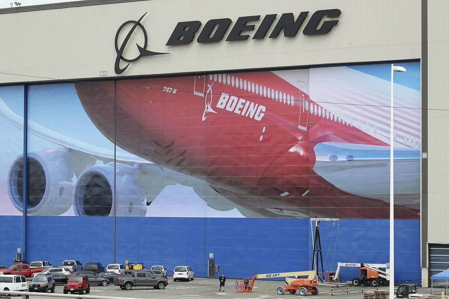 A worker walks near a mural of a Boeing 747-8 airplane at the company's manufacturing facility in Everett, Wash., Monday, March 23, 2020, north of Seattle. Boeing announced Monday that it will be suspending operations and production at its Seattle area facilities due to the spread of the new coronavirus. (AP Photo/Ted S. Warren) Photo: Ted S. Warren, Associated Press