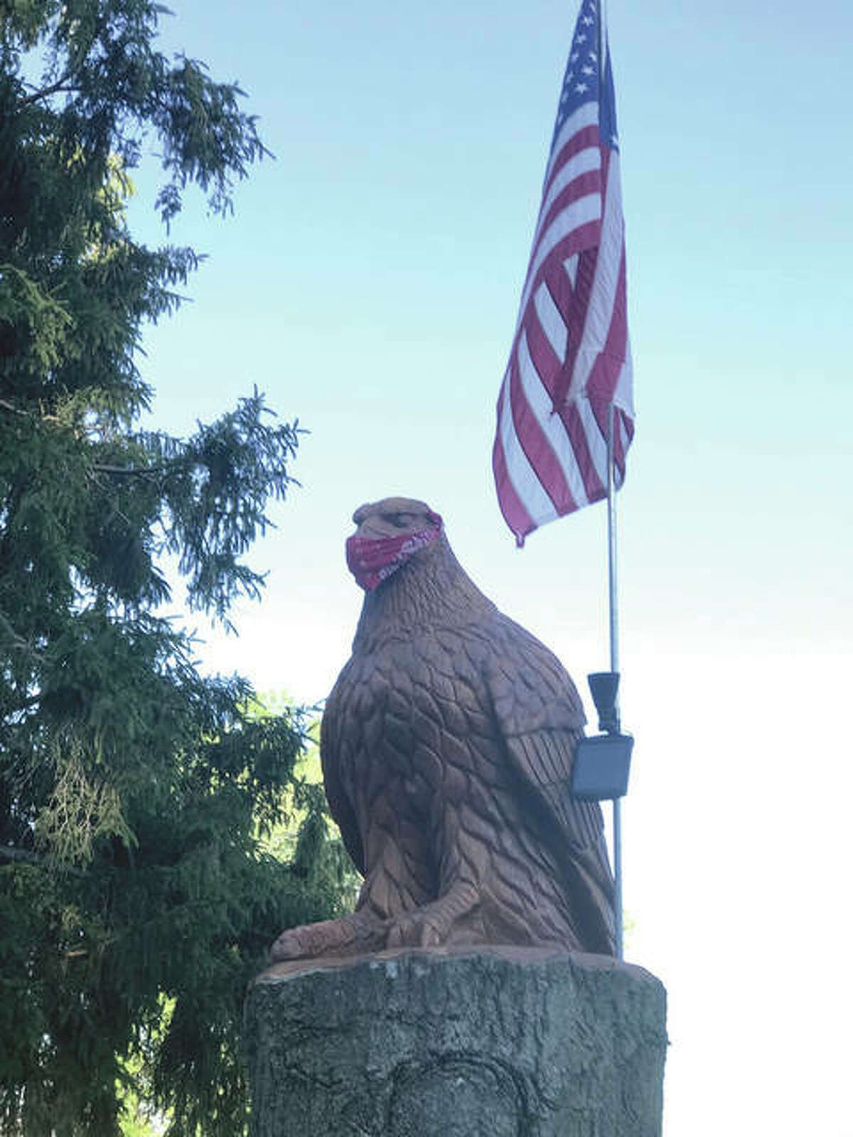 An eagle sculpture isn't taking any chances as it sports a face covering near Franklin.