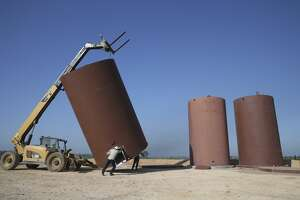 A roustabout crew works on a setting up oil containers at a drilling site by Millennium Exploration south of Gonzales, Texas, Friday, April 24, 2020. They installed three tanks that hold 400 barrels of oil each and also a fiberglass tank for saltwater. The company drilled Chalk Talk #2 to a depth of 8,600 feet and went 4,000 feet horizontally. They expect 800 barrels a day from the well.