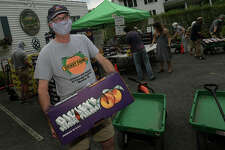 Food writer Frank Whitman visits the famous Georgia Peach Truck as ir olls into Gilberties Herb Farm Friday, July 3, 2020, in Westport, Conn. The truck rolled onto Darien and Greenwich on Friday and then to Stamford on Sunday.