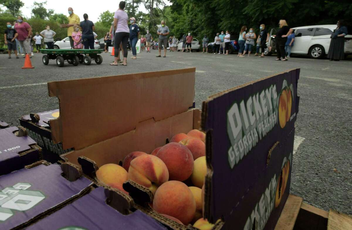 Hundreds of customers turn up to meet the famous Georgia Peach Truck as it rolls into Gilberties Herb Farm Friday, July 3, 2020, in Westport, Conn. The truck rolled onto Darien and Greenwich as well on Friday and then to Stamford on Sunday.