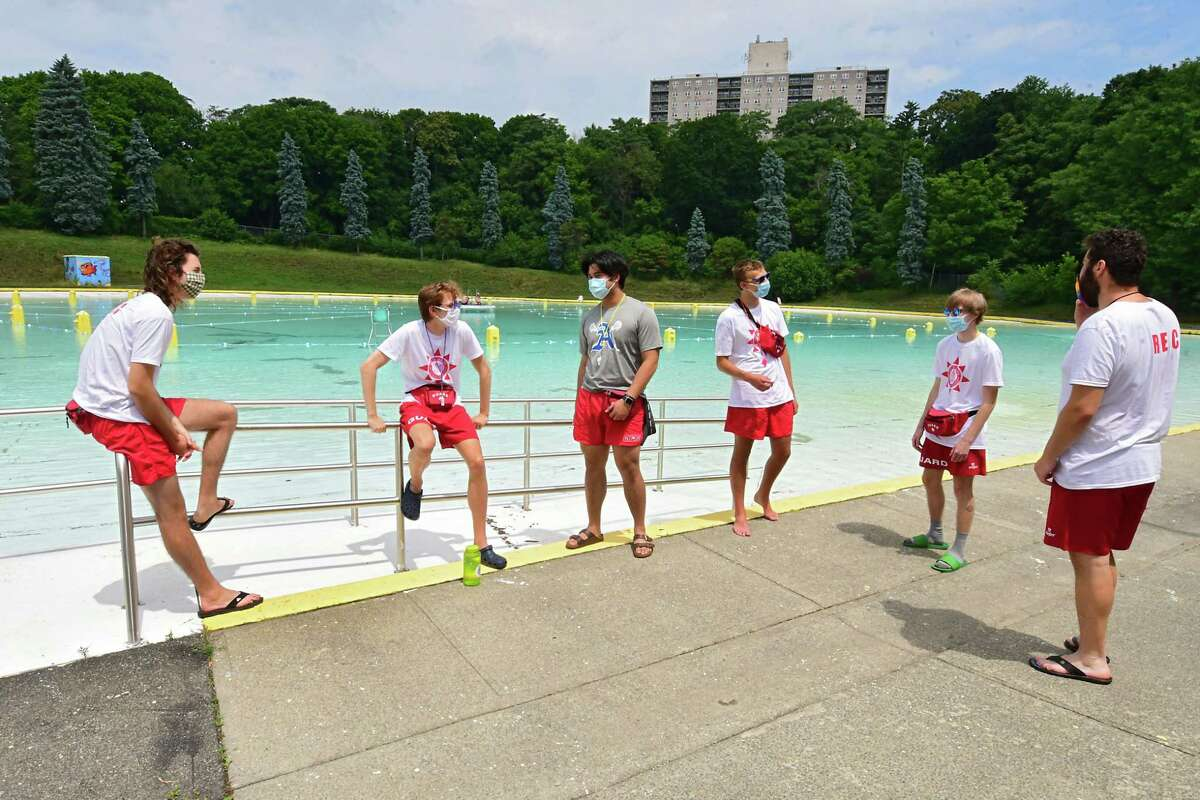 Lifeguards wear protective face masks and practice social distancing as they talk about the day's plans moments before the Lincoln Park pool opens for the season on Friday, July 3, 2020 in Albany, N.Y. (Lori Van Buren/Times Union)