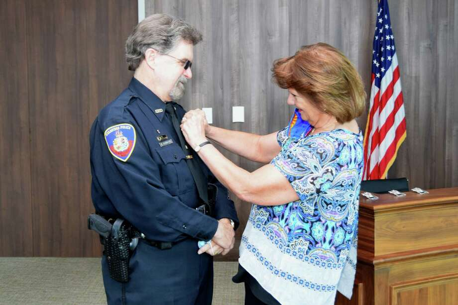 Ed Rondano, Stamford's longest-serving patrol officer, gets Badge 1 pinned to his uniform by his wife, Kathy, at a special ceremony at Stamford Police headquarters on Monday. Photo: Stamford Police Department / Contributed