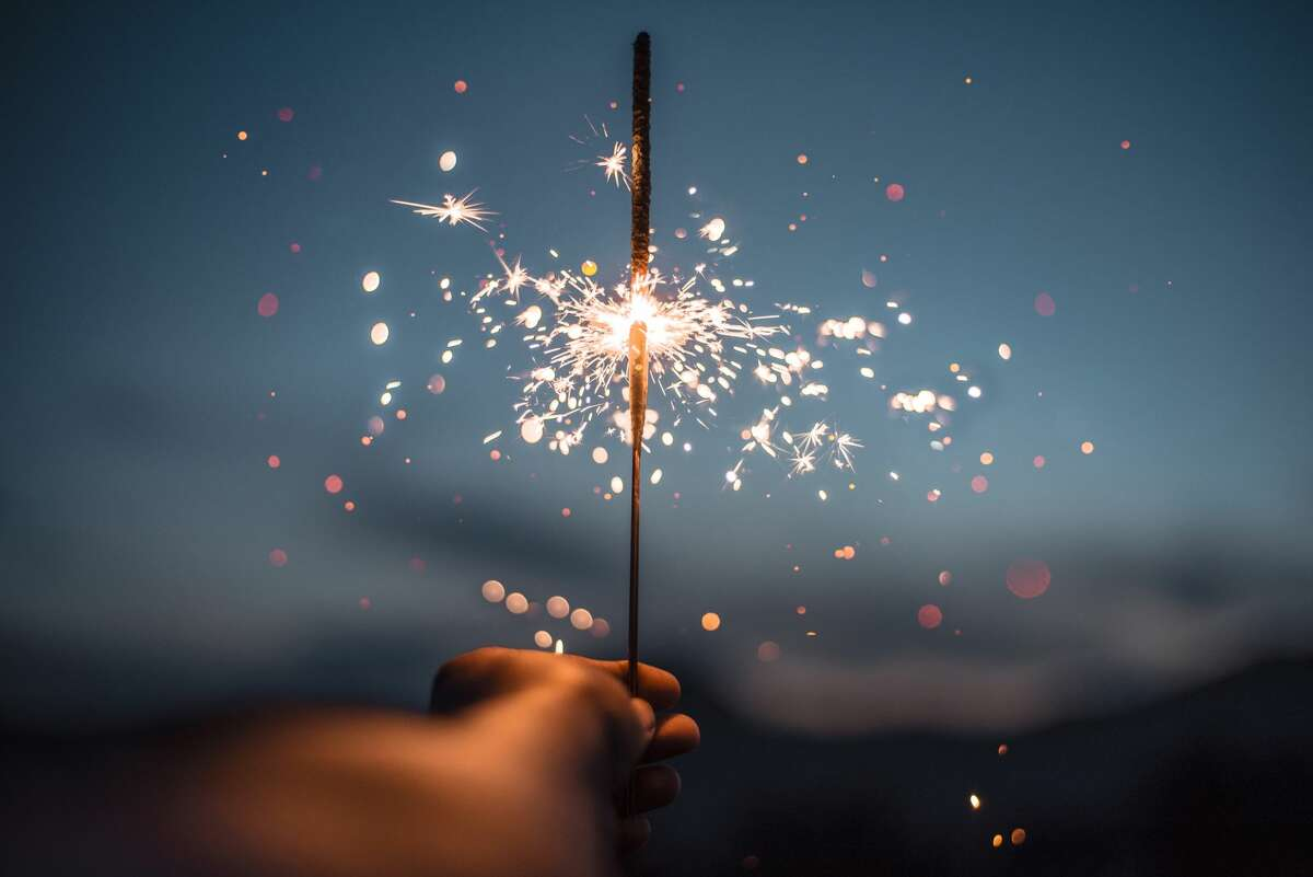 A sparkler lights up the approaching nightfall.